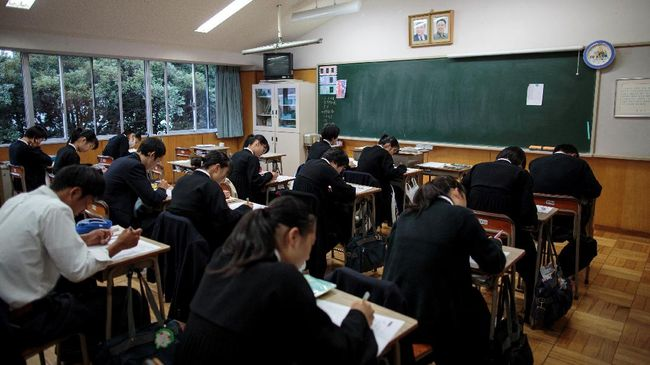 In this picture taken on October 13, 2017, students take an exam as portraits of late North Korean leaders Kim Il Sung and Kim Jong Il are seen in a classroom at Tokyo Korean high school in Tokyo. Portraits of North Korea's late leaders hang proudly in the classrooms of the Korean High School in Tokyo, where the recent surge in tensions over Pyongyangís nuclear weapons programme have seen faculty and staff subjected to death threats. / AFP PHOTO / Behrouz MEHRI / TO GO WITH AFP STORY JAPAN-NKOREA-SKOREA-SOCIETY-EDUCATION BY HARUMI OZAWA