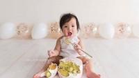 <p>Makan cake-nya pakai sendok, bakal cemong nggak ya si kecil yang satu ini? (Foto: Instagram/ @bumblebboutique) </p>