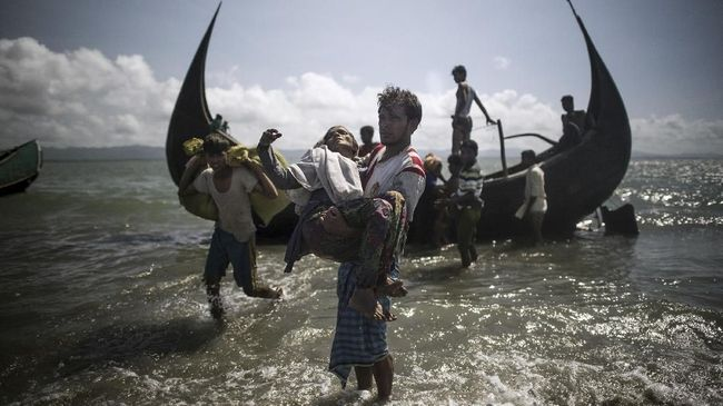 A Bangladeshi man helps Rohingya Muslim refugees to disembark from a boat on the Bangladeshi shoreline of the Naf river after crossing the border from Myanmar in Teknaf on September 30, 2017. More than 2,000 Rohingya have massed along Myanmar's coast this week after trekking from inland villages in Rakhine state to join the refugee exodus to Bangladesh, state media reported September 30. They follow more than half a million fellow Rohingya who have emptied out of northern Rakhine in a single month, fleeing an army crackdown and communal violence the UN says amounts to