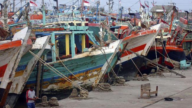Nelayan berada di samping kapal cantrang saat tidak melaut di Pelabuhan Jongor, Tegal, Jawa Tengah, Minggu (31/12). Larangan alat tangkap cantrang mulai 1 Januari 2018 oleh Kementerian Kelautan dan Perikanan (KKP), membuat ratusan kapal di daerah tersebut tidak melaut dan diharuskan mengganti alat tangkap. ANTARA FOTO/Oky Lukmansyah/aww/17.