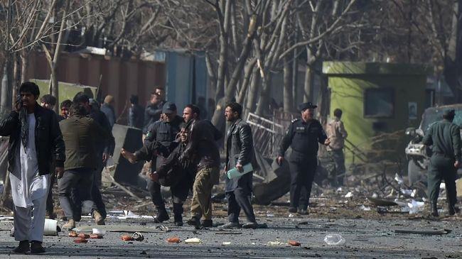 Afghan volunteers and policemen help wounded at the scene of a car bomb exploded in front of the old Interior Ministry building in Kabul on January 27, 2018. An ambulance packed with explosives blew up in a crowded area of Kabul on January 27, killing at least 17 people and wounding 110 others, officials said, in an attack claimed by the Taliban.  / AFP PHOTO / WAKIL KOHSAR