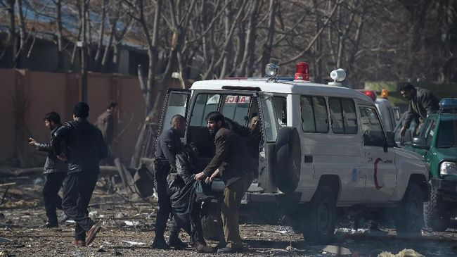 Afghan volunteers and policemen carry injured men on an ambulance at the scene of a car bomb exploded in front of the old Ministry of Interior building in Kabul on January 27, 2018.