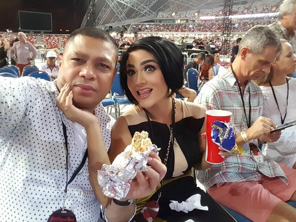 Ini saat Krisdayanti dan Raul Lemos nonton konser Madonna di Singapur. Mereka terlihat menikmati sandwich dan satu gelas minuman bersoda. Foto: Instagram @raullemos06