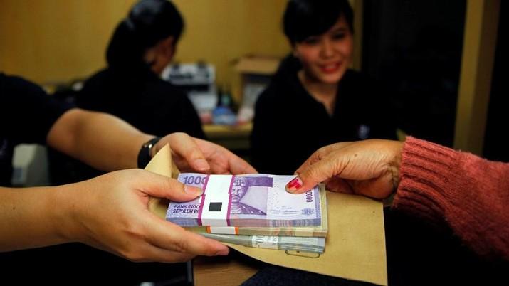 FILE PHOTO: A woman holds Indonesian rupiah banknotes at a Bank Negara Indonesia (BNI) mobile bank in Jakarta July 15, 2013.   REUTERS/Beawiharta/File Photo