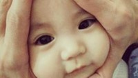 <p>Hal terpenting dalam melakukan pose onigiri baby adalah tidak mencengkeram erat wajah bayi. Hiks, kasihan, nanti bayinya nggak nyaman. Ya, tangan kita cuma membingkai lembut wajahnya dengan posisi jari-jari tangan membentuk segitiga menyerupai onigiri. (Foto: Instagram @jillyteh)</p>