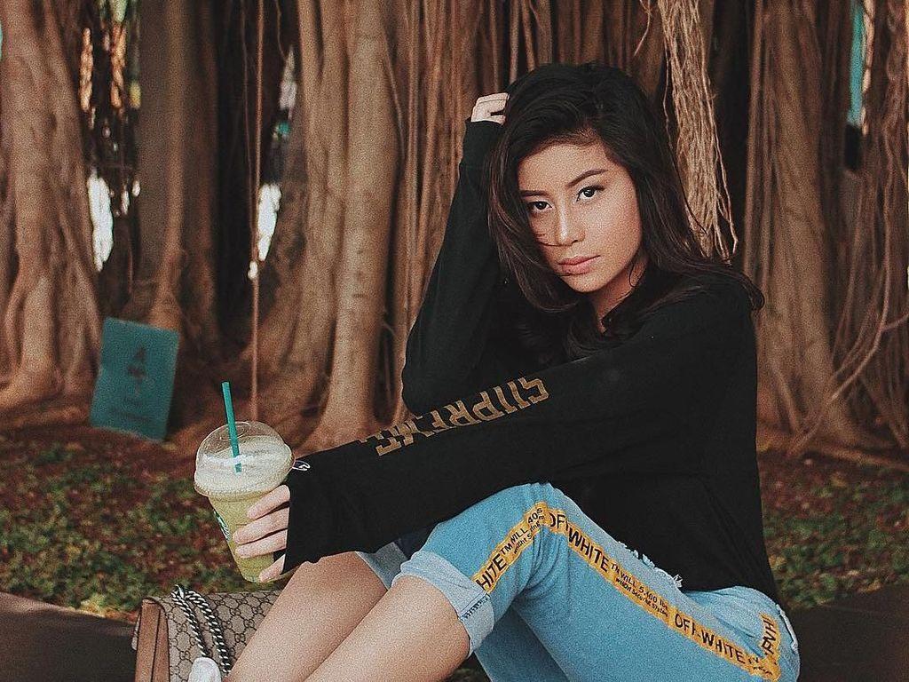 Awkarin minum segelas greentea latte di bawah pohon besar. Lagi ngadem ya? Foto: Instagram @awkarin