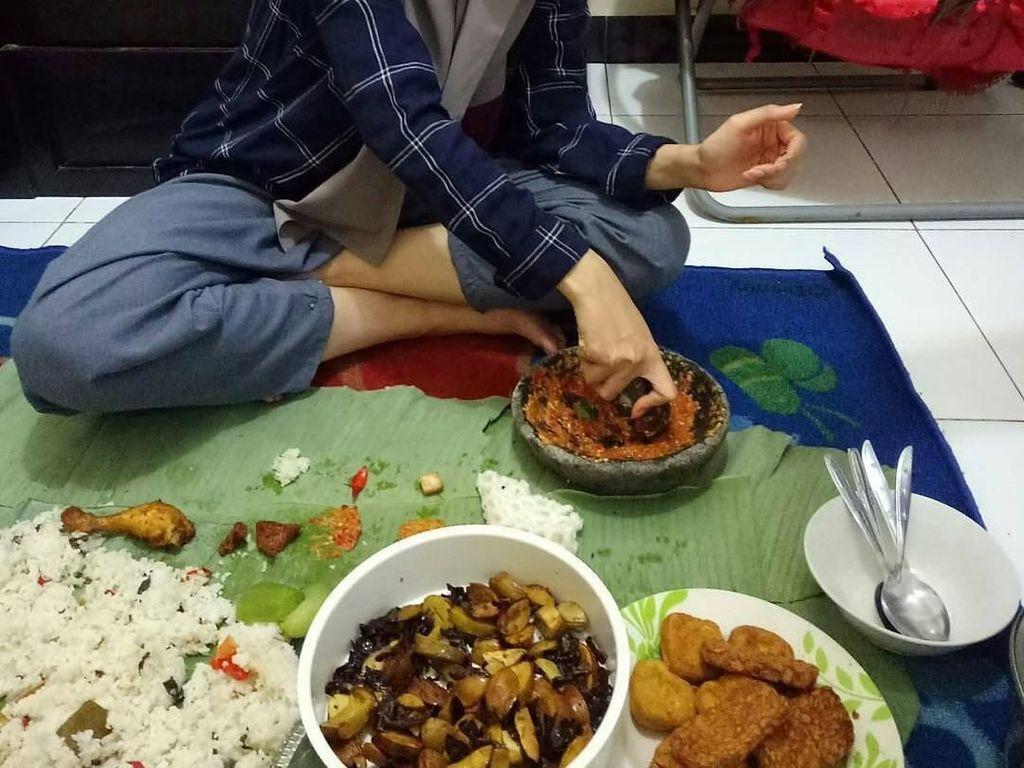 Duh, Rina Nose ngulek sambal sendiri buat dicampur jengkol goreng plus tahu dan tempe goreng di depannya. Dimakan pakai nasi liwet beralaskan daun pisang pasti lezat. Jadi mau, deh! Foto: Instagram @wantocah_wonosobo