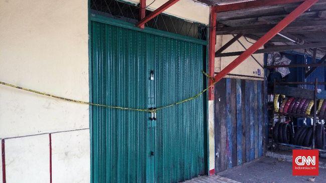 Pita kuning garis polisi melintang di pintu geser berkelir hijau. Sampah berserakan dan bau oli menyeruak di warung yang menjual miras perenggut nyawa itu.