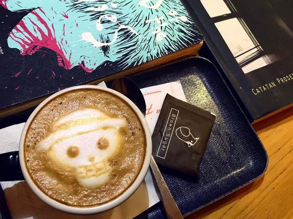Ada segelas cappucino hangat di samping buku yang tengah dibaca Sherina. Kali ini kopinya diberi latte art gambar tengkorak bertopi. Foto: Instagram @sherinasinna