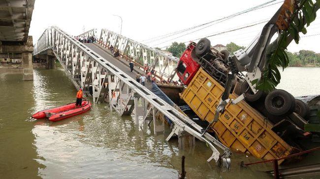 Alat berat mengevakuasi tiga truk di Jembatan Widang yang tercebur ke Bengawan Solo akibat ambrolnya jembatan tersebut.