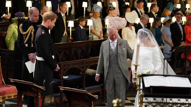 Meghan Markle lalu disambut Pangeran Charles yang mengantarkannya berjalan ke altar. Seharusnya ayahnya, Thomas Markle yang melakukan itu, namun mendadak ia batal hair. (Jonathan Brady/Pool via REUTERS)