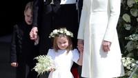 Tuh lihat, Putri Charlotte memamerkan senyum manis sambil menggandeng tangan ibunya, Kate Middleton. Sementara sang kakak, Pangeran George, sepertinya kepanasan tuh. (Foto: Getty Images)