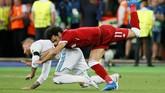 Sergio Ramos dan Mohamed Salah terlibat dalam duel pada laga final Liga Champions 2018. Setelah insiden tersebut, Salah ditarik keluar karena mengalami cedera bahu. (REUTERS/Gleb Garanich)