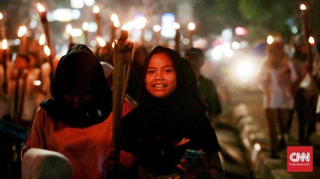 Masyarakat Ibu kota Jakarta warga merayakan malam takbiran dengan pawai obor keliling menyusuri jalan raya. Malam ini masyarakat akan merayakan takbiran untuk menyambut Hari Raya Idul Fitri 1439 Hijriah. Jakarta. Kamis,14 Juni 2018.CNN Indonesia/Andry Novelino