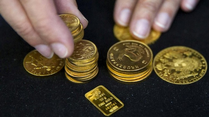 FILE PHOTO: A worker places gold coins on display at Hatton Garden Metals precious metal dealers in London, Britain July 21, 2015. REUTERS/Neil Hall/File Photo - PT Rifan