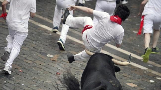 Tak sedikit yang mengalami sakit ketika tanduk tajam si banteng menyeruduk tubuh. Beberapa mengalami luka, namun ada juga yang nyaris tewas. (REUTERS/Vincent West)