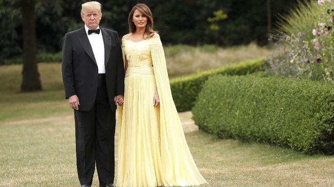 Saat gala dinner bersama Theresa May, Melania Trump terlihar segar dengan gaun cape kuningnya buatan J. Mendel