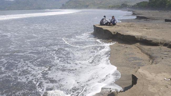 Sepasang wisatawan duduk di pantai Sidem yang mengalami abrasi, Tulungagung, Jawa Timur, Jumat (20/7). Meski berada di area Teluk Popoh, gelombang tinggi yang terjadi sejak dua hari terakhir telah menyebabkan kawasan pesisir pantai ini mengalami abrasi. ANTARA FOTO/Destyan Sujarwoko/foc/18.