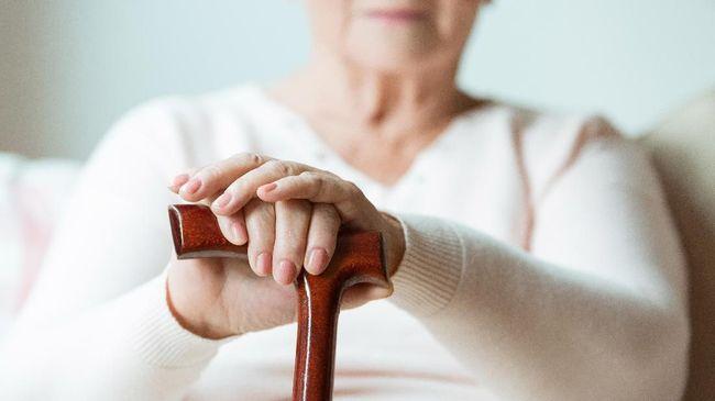 Elder holds hands on walking stick while sitting on white sofa in nursing home