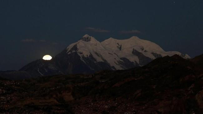 Dari Pegununan Illimani, La Paz, Bolovia, gerhana bulan terlihat menyembul. Total proses gerhana bulan kali ini adalah selama 6,5 jam. (Reuters/David Mercado)