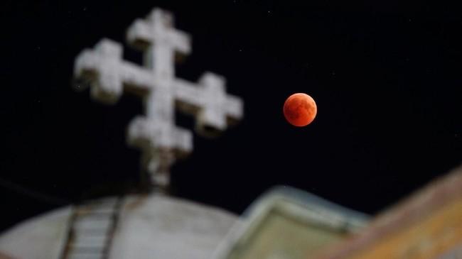 Dari sebuah Gereja Ortodoks Koptik di Amman, Yordania, gerhana bulan terlihat berwarna kemerahan. Mars akan terlihat terang dan hujan meteor juga terjadi bersamaan dengan gerhana bulan. (Reuters/Muhammad Hamed)