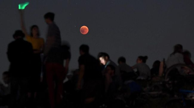 People watch the total lunar eclipse in the Olympic park in Munich, southern Germany, on July 27, 2018.  The longest