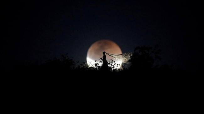 Seorang pengantin di Brasilia, Brazil, berfoto ketika gerhana bulan total atau