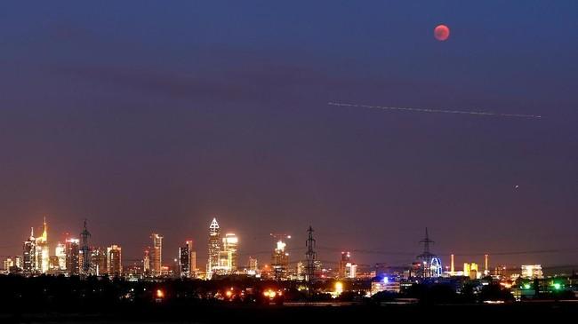 Gerhana bulan di langit Frankfurt, Jerman. Gerhana bulan kali ini merupakan yang terpanjang di abad ini, selama 1 jam 43 menit. (Reuters/Kai Pfaffenbach)