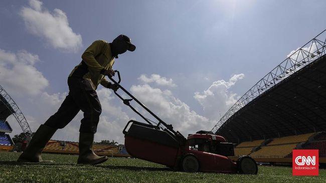 Pekerja merapihkan rumput Stadion Bumi Sriwijaya di kawasan Jakabaring Sport City. Palembang, Kamis, 25 Juli 2018. CNNIndonesia/Adhi Wicaksono.