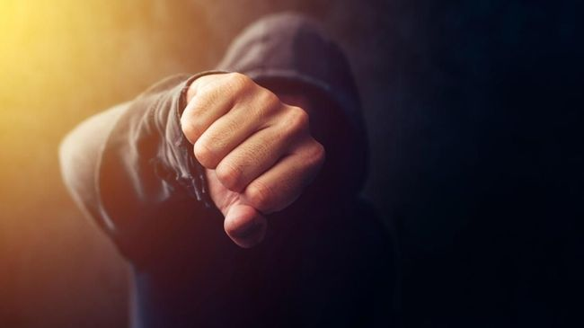 Crime, violence and bullying concept with hooded criminal person, selective focus on fist