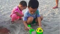 <p>Kakak adik itu mengisi liburan dengan kompak bermain pasir di pantai. (Foto: Instagram @shezy_idris)</p>