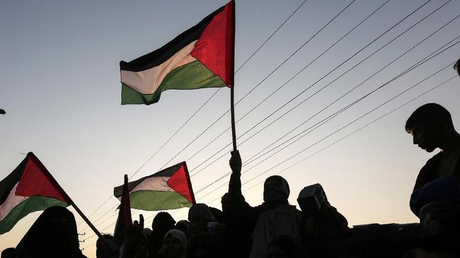 Palestinian protesters wave their national flags at sunset during a demonstration near the Erez crossing with Israel on September 4, 2018, in the northern Gaza Strip protesting against the United States decision to stop funding and backing the United Nations agency for Palestinian refugees(UNRWA).  / AFP PHOTO / MAHMUD HAMS