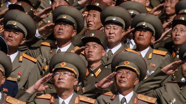 Korean People's Army (KPA) soldiers salute as they watch a mass rally on Kim Il Sung square in Pyongyang on September 9, 2018. North Korea held a military parade to mark its 70th birthday, but refrained from showing off the intercontinental ballistic missiles that have seen it hit with multiple international sanctions. / AFP PHOTO / Ed JONES