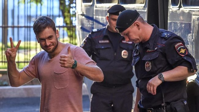 Member of the Pussy Riot punk group Pyotr Verzilov (L) gestures as he walks with police during a court hearing at a courthouse in Moscow, on July 31, 2018, as members of the Russian protest-art group are accused of disturbing public order after invading the pitch during the World Cup final in Moscow. Russian police on July 30 detained four members of the Pussy Riot punk group immediately after they were released from custody, having served 15 days for invading the pitch at the World Cup final in Moscow. On July 31 they were released again from prison only to be detained once more, and brought to court for a hearing. / AFP PHOTO / Vasily MAXIMOV