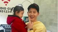 <p>Kalau yang ini anaknya malu-malu, Bun. Nggak apa-apa deh yang penting udah foto bareng Song Joong Ki. (Foto: Instagram @songjoongkionly)</p>