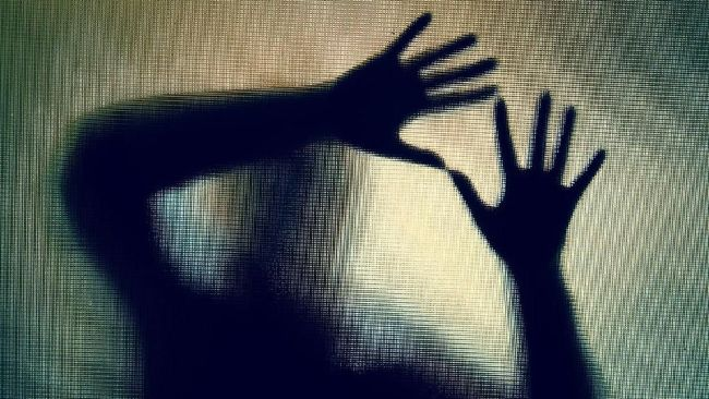 Colour backlit image of the silhouette of a woman with her hands pressed against a glass window. The silhouette is distorted, and the arms elongated, giving an alien-like quality. The image is sinister and foreboding, with an element of horror. It is as if the 'woman' is trying to escape from behind the glass. Horizontal image with copy space.