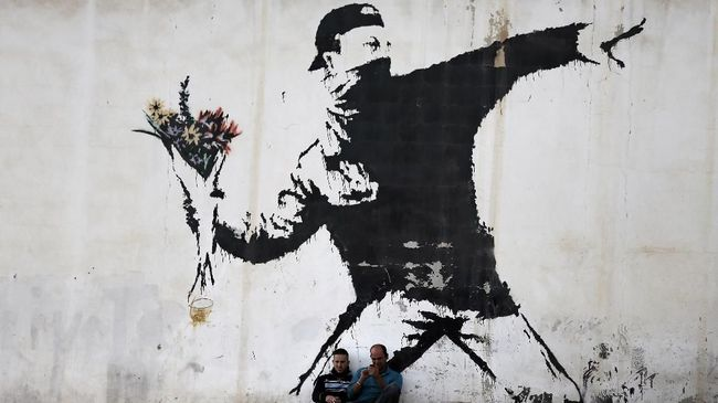 Two men are sitting in front of a famous graffiti of British street artist Banksy, painted on a wall of a gas station in the West Bank city of Bethlehem on December 16, 2015. AFP PHOTO / THOMAS COEX / AFP PHOTO / THOMAS COEX