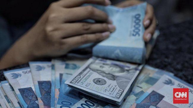 Petugas memperlihatkan pecahan uang dolar dan rupiah di salah satu tempat penukaran mata uang asing, Jakarta (10/10). Saat ini nilai tukar rupiah terhadap dolar berada di posisi Rp. 15.222 per dolar Amerika Serikat.
