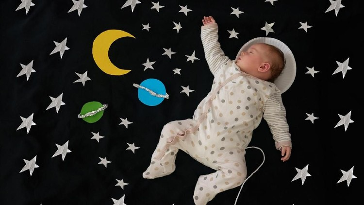 Conceptual shot of a baby girl as an astronaut against a space background