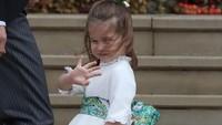 <p>Kondisi berangin kencang tak menyurutkan semangat Putri Charlotte untuk jadi pengiring pengantin. (Foto: Steve Parsons - WPA Pool/Getty Images)</p>