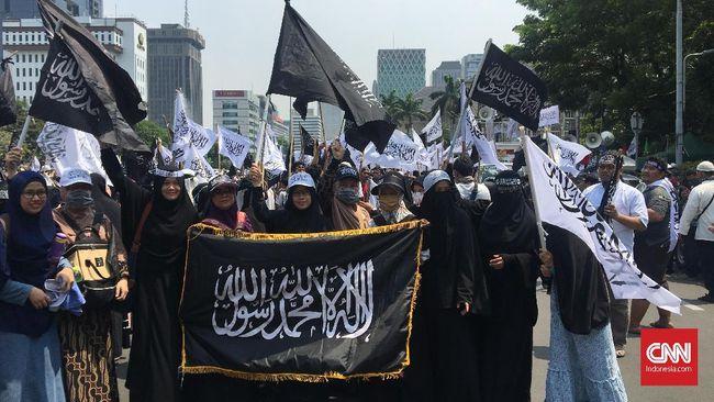 Massa membawa spanduk bertuliskan 'Bubarkan Banser' saat Aksi Bela Tauhid di kantor Kemenko Polhukam. Menko Polhukam Wiranto sendiri dikabarkan berada di Palu.