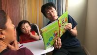 <p>Steve Yeun lagi bacakan si kecil buku apa ya? (Foto: Instagram/jopakka)</p>