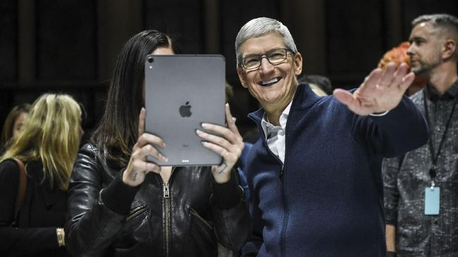 NEW YORK, NY - OCTOBER 30: Tim Cook, CEO of Apple laughs while Lana Del Rey (with iPad) takes a photo during a launch event at the Brooklyn Academy of Music on October 30, 2018 in New York City. Apple debuted a new MacBook Air, Mac Mini and iPad Pro.   Stephanie Keith/Getty Images/AFP