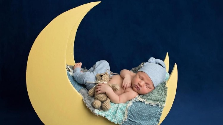 Studio portrait of a ten day old newborn baby boy wearing pajama bottoms and a sleeping cap. He is sleeping on a moon shaped posing prop and holding a Teddy Bear.