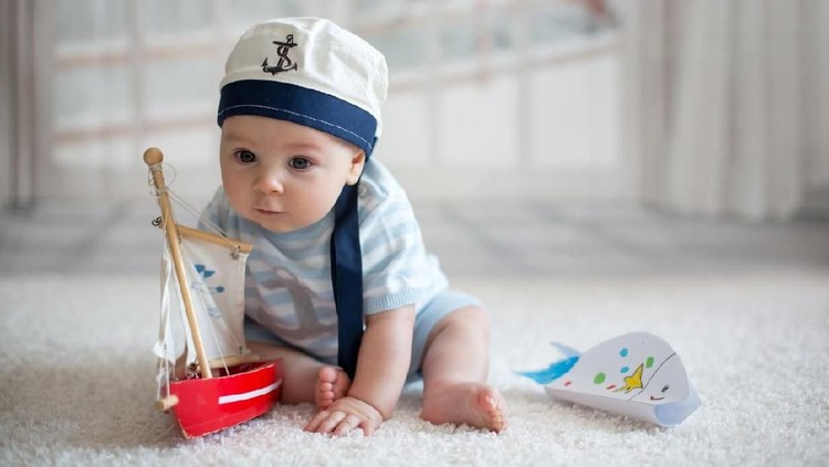 Little baby boy, playing wtih little boat and little fish at home, having sailor hat