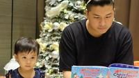 <p>Lucu banget ya foto Natal keluarga mereka. Glenn Alinskie membacakan dongeng Natal untuk si cantik Natusha. (Foto: Instagram @ glennalinskie) </p>
