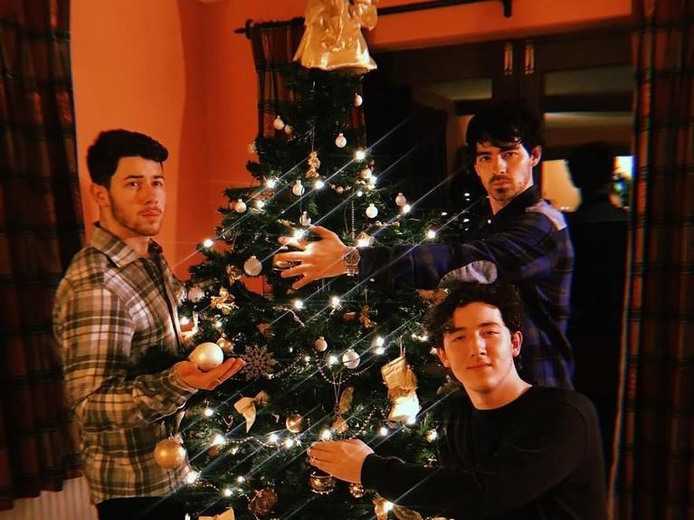 Selain itu, Nick juga menyempatkan foto bersama saudaranya, Joe Jonas dan Franklin Jonas. Ketiganya berfoto bersama pohon Natal mereka.