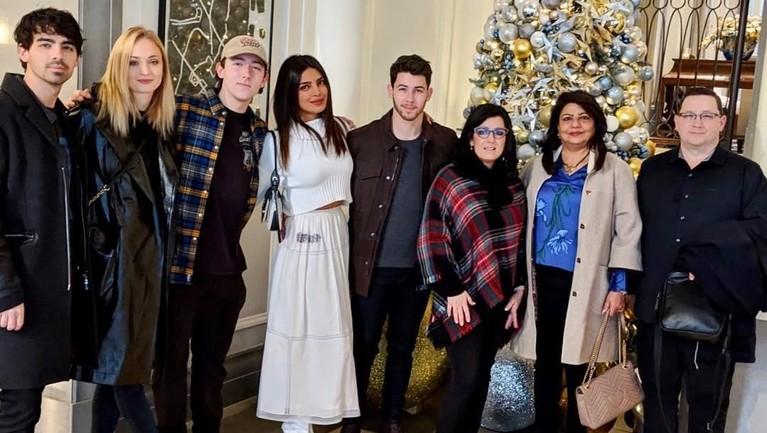 Priyanka datang mengunjungi keluarga Jonas. Perempuan 36 tahun itu berfoto bersama keluarga Nick dan pohon natalnya.