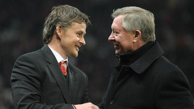 Former Manchester United footballer and reserve team coach, Norweigan Ole Gunner Solskjaer (L) receives a gift of appreciation after 14 years service at the club from manager Sir Alex Ferguson ahead of the English Premier League football match between Manchester United and Arsenal at Old Trafford in Manchester, north-west England on December 13, 2010. Solskjaer has left the clu to become manager of Norweigan team Molde. AFP PHOTO/ANDREW YATES --- RESTRICTED TO EDITORIAL USE Additional licence required for any commercial/promotional use or use on TV or internet (except identical online version of newspaper) of Premier League/Football League photos. Tel DataCo +44 207 2981656. Do not alter/modify photo (Photo by ANDREW YATES / AFP)