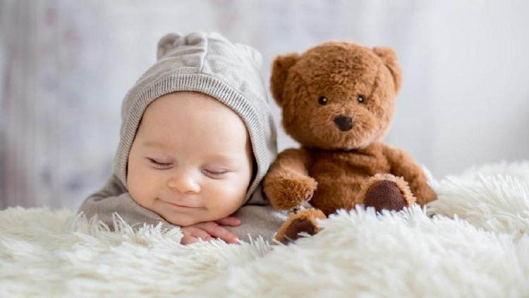 Sweet baby boy in bear overall, sleeping in bed with teddy bear stuffed toys, winter landscape behind him